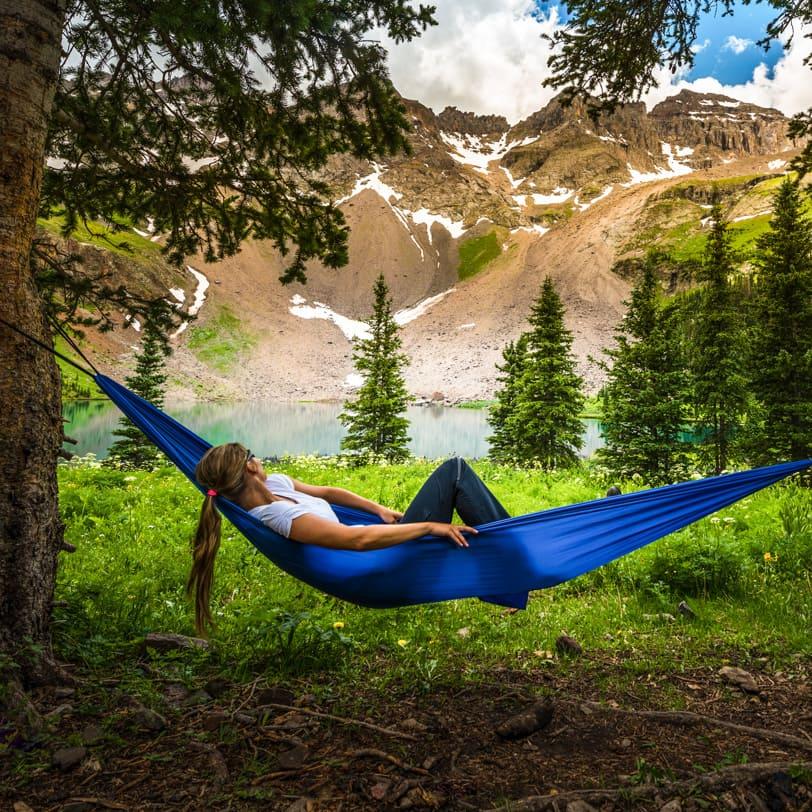 Woman in a hammock near a mountain lake