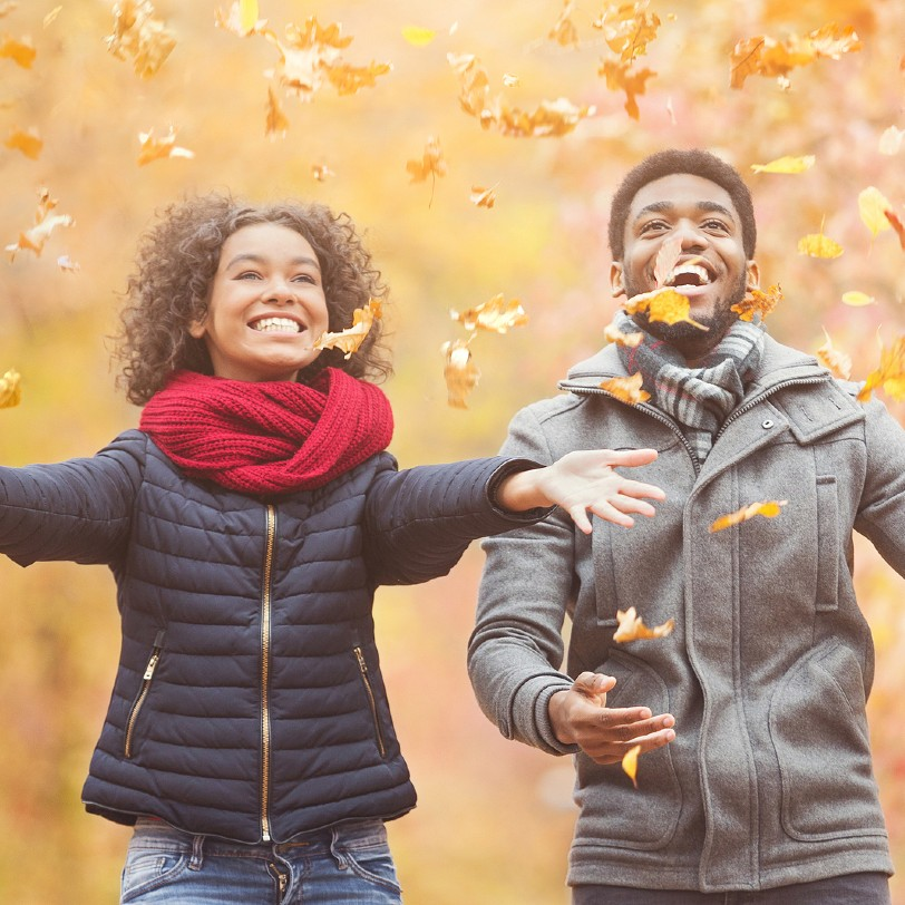 couple throwing fall leaves