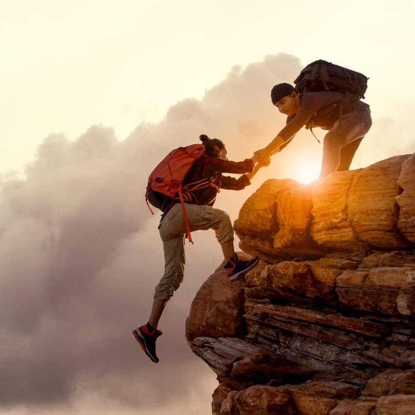 Two people climbing a rock
