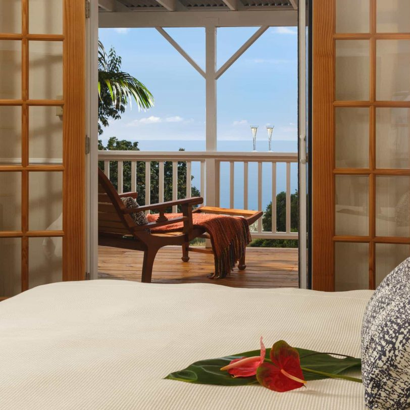 a bed with an open door to a balcony with an ocean view
