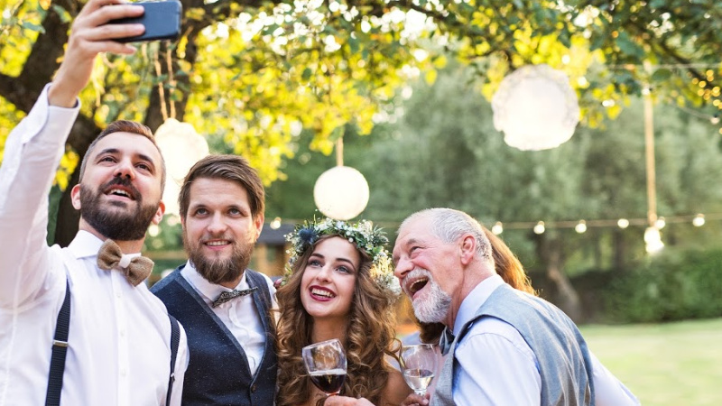 A bride and groom taking a selfie with the wedding party- tip 7 for wedding marketing