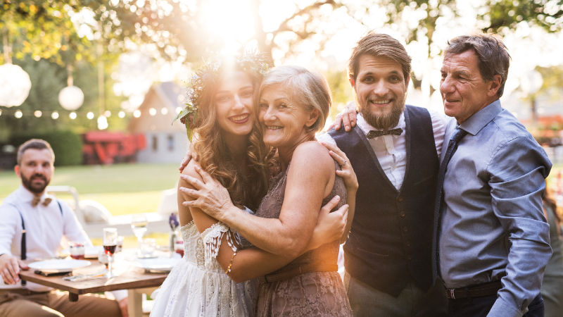 A Bride and her family taking a picture at an outdoor wedding- tip 4 for wedding marketing