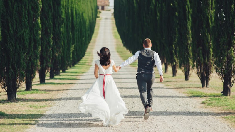 Bride and groom walking on a country lane - tip 1 for wedding business marketing
