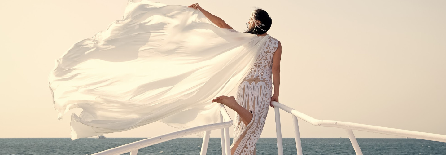 Bride on a Boat with veil blowing in the wind