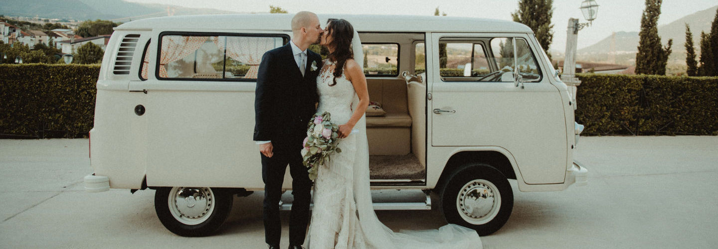 Bride and groom kissing in front of the getaway car