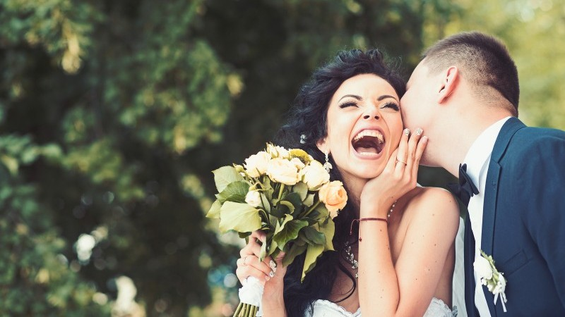 Groom kissing bride holding bouquet