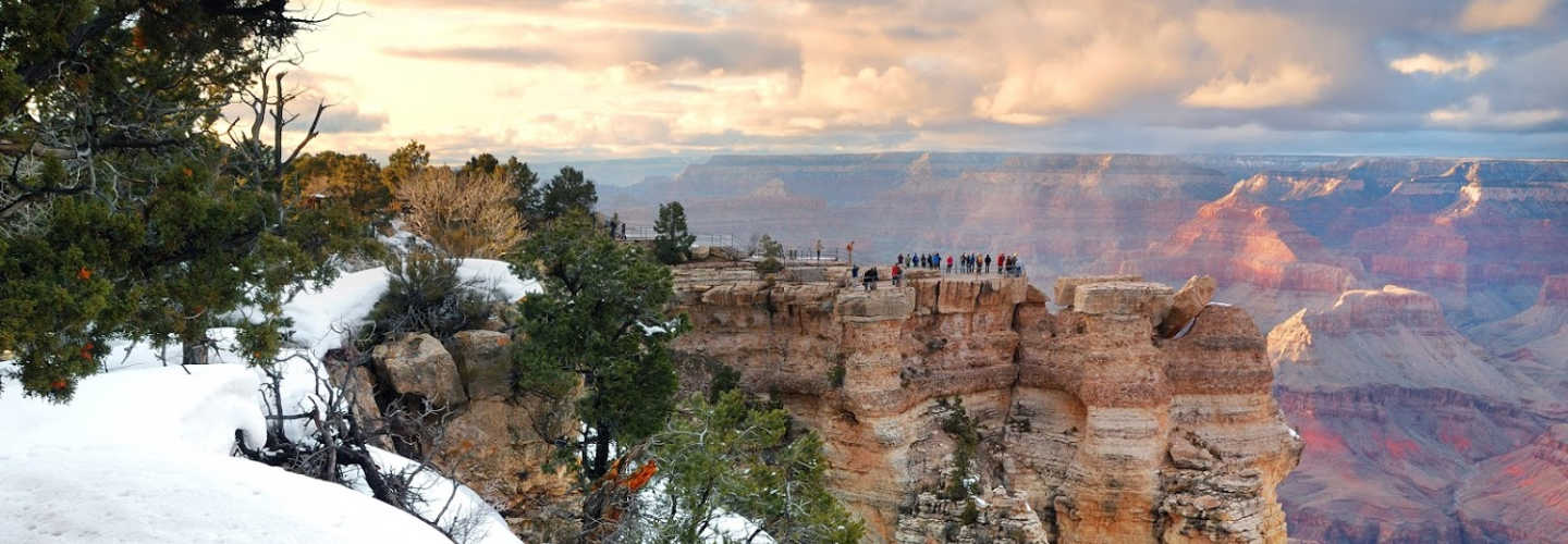 an observation platform over the grand canyon with snow and visitors