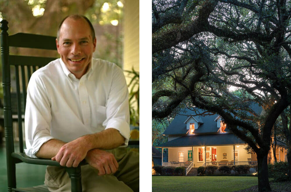 Portrait of a man in a green rocking chair on the left - on the right is a beautiful historic home illuminated at night surrounded by oak trees