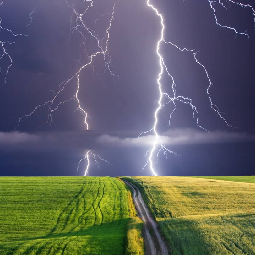 two bolts of lightning striking a field