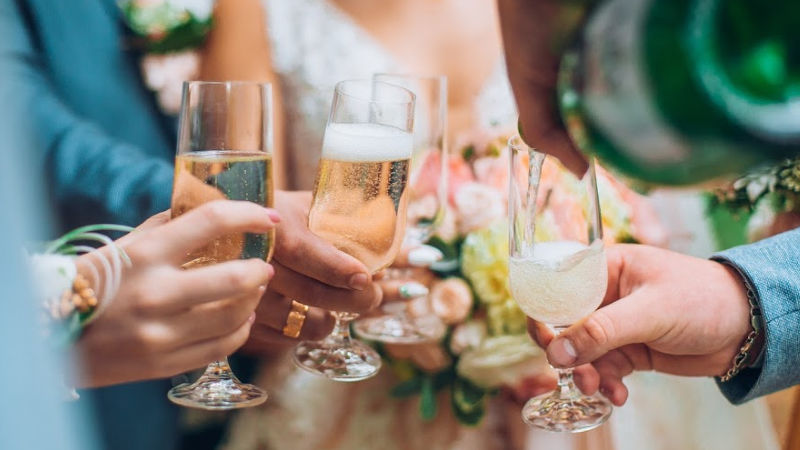 People drinking champagne at a wedding- tip 2 for wedding marketing