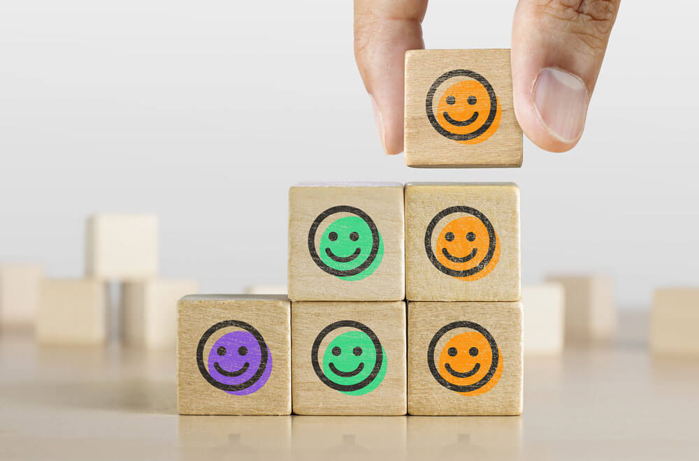 Wooden blocks with smiling faces stacked in an upward motion to imply success