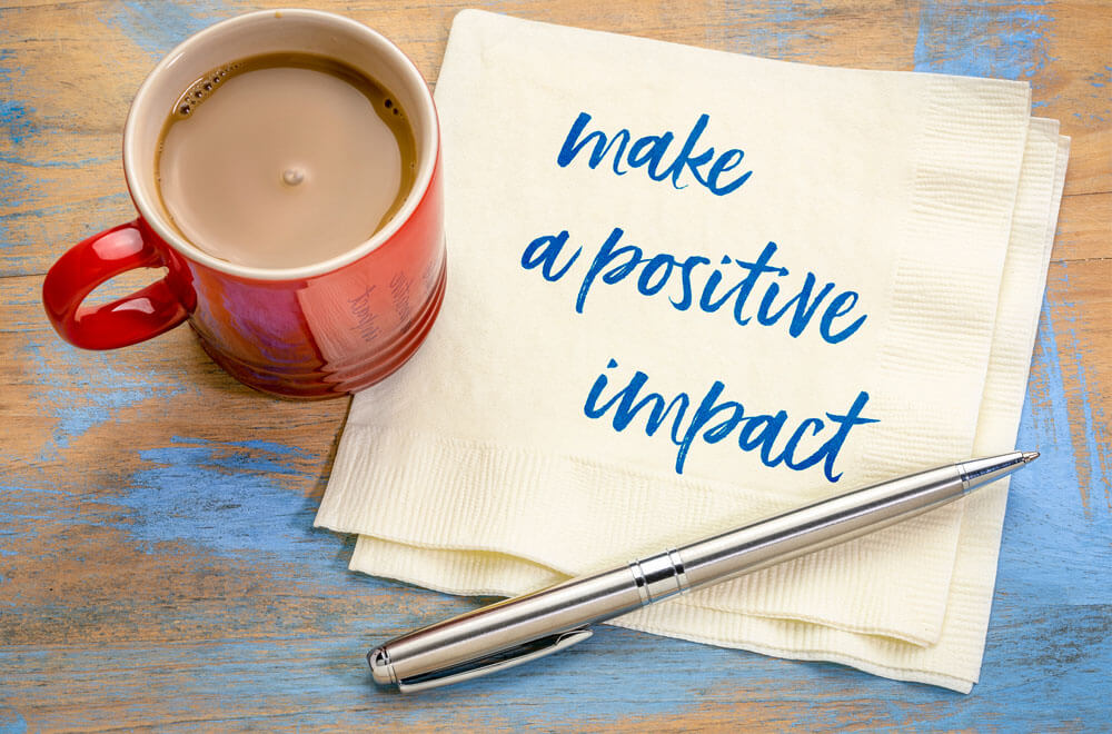 Red Coffee cup on a napkin that says Make a Positive Impact