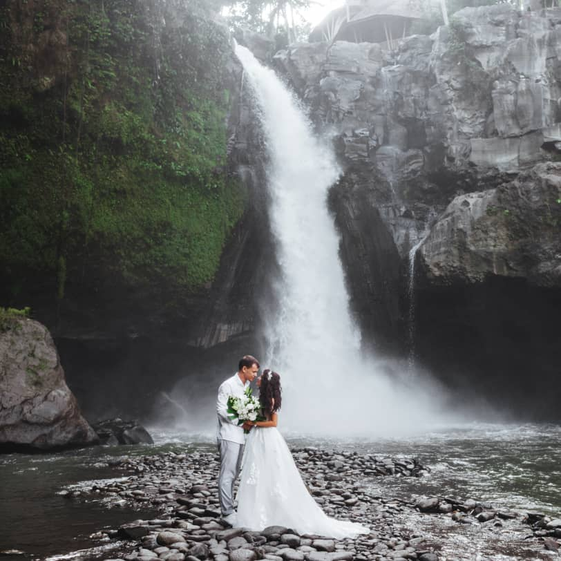 Couple standing in front of a large waterfall
