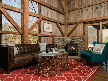 Granary living room with fireplace, leather couch, and teal chair
