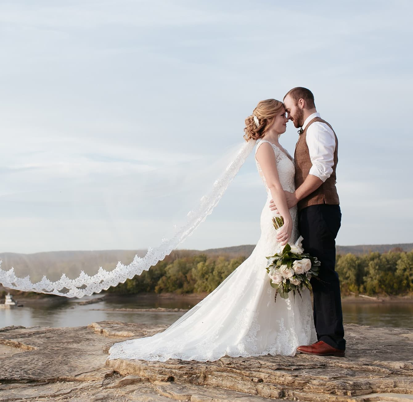 Wedding couple standing on a stone in front of a river
