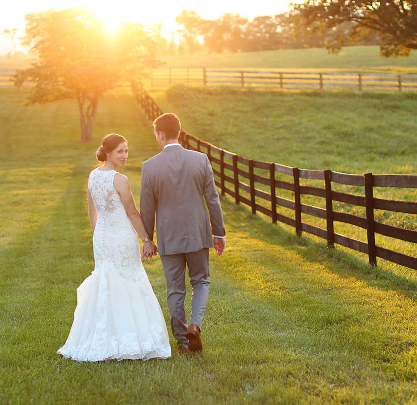 Bride and groom walking on green grass at sunset