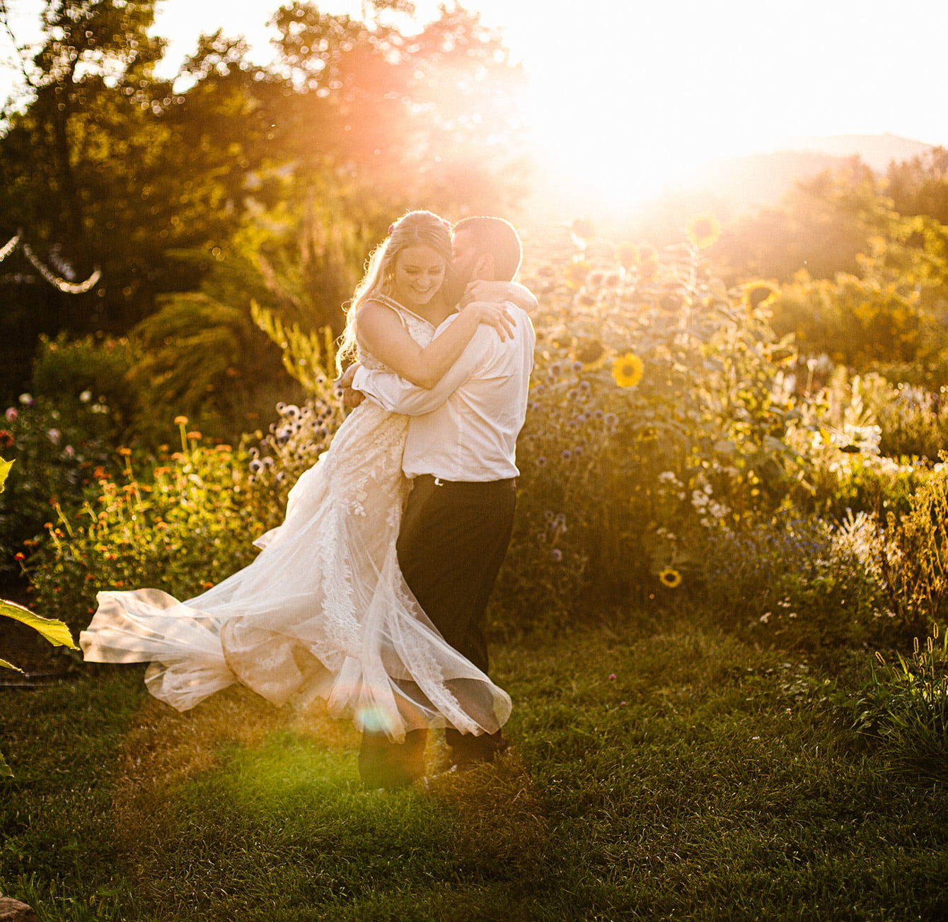 Bride and groom dancing in flowers at sunset