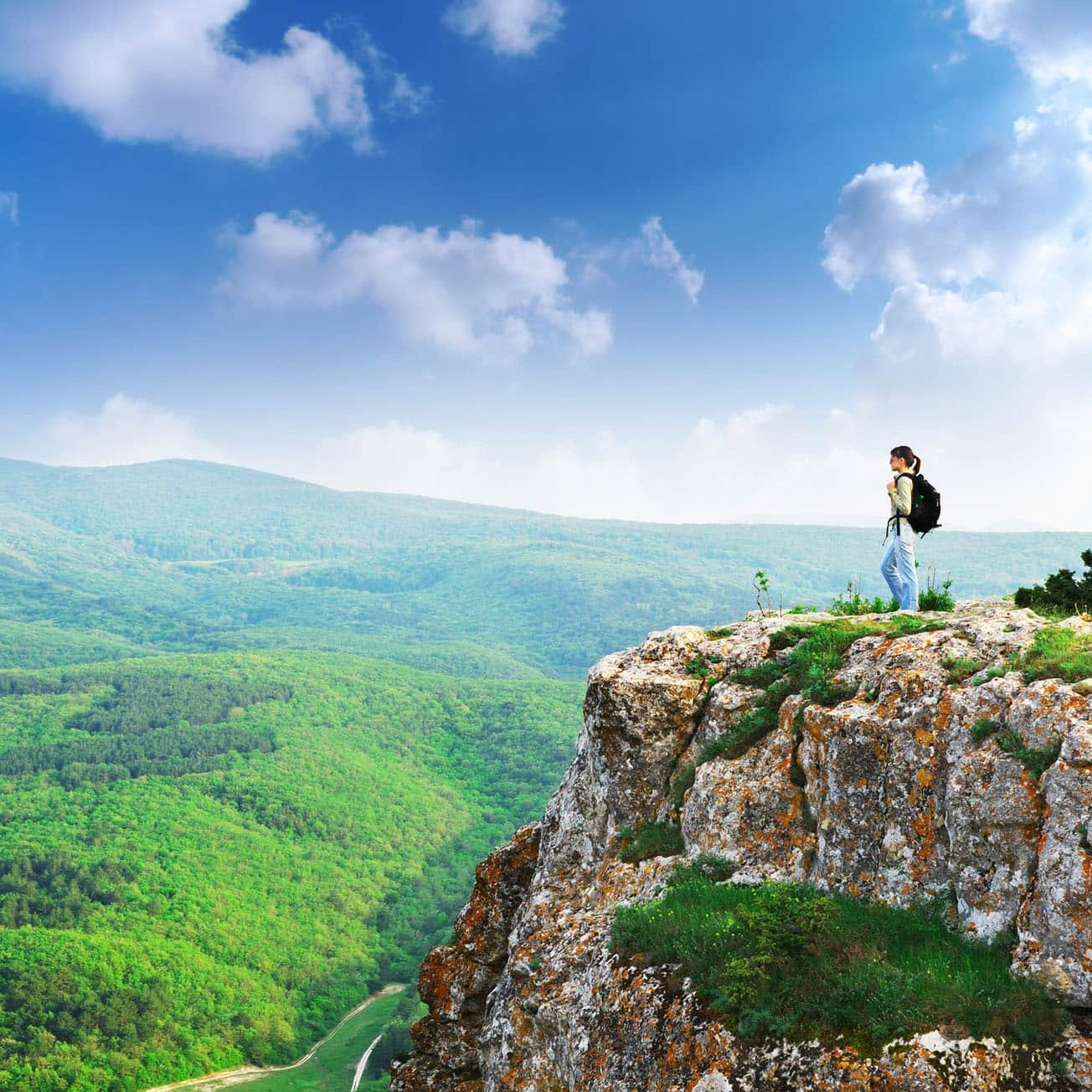 Woman standing on a vista overlooking a green landscape