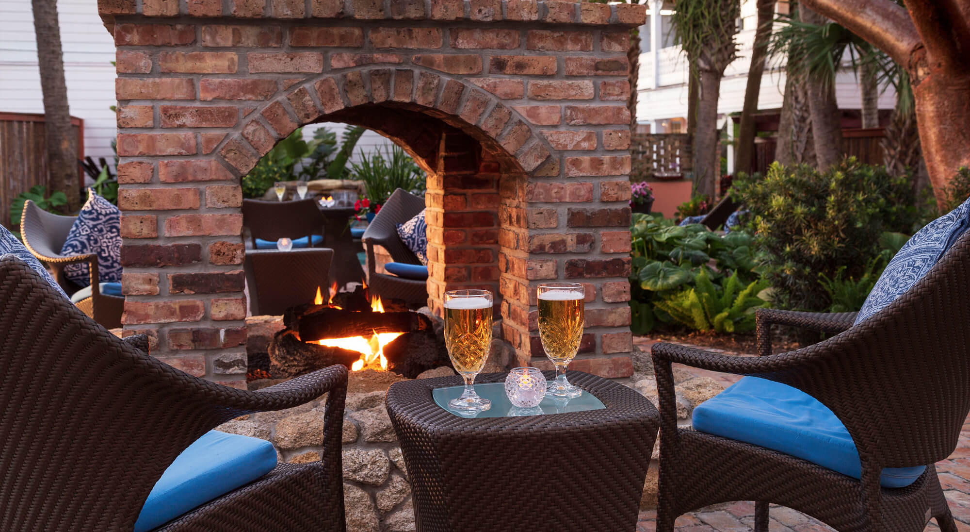 Two chairs with two beers in front of an outdoor brick fireplace