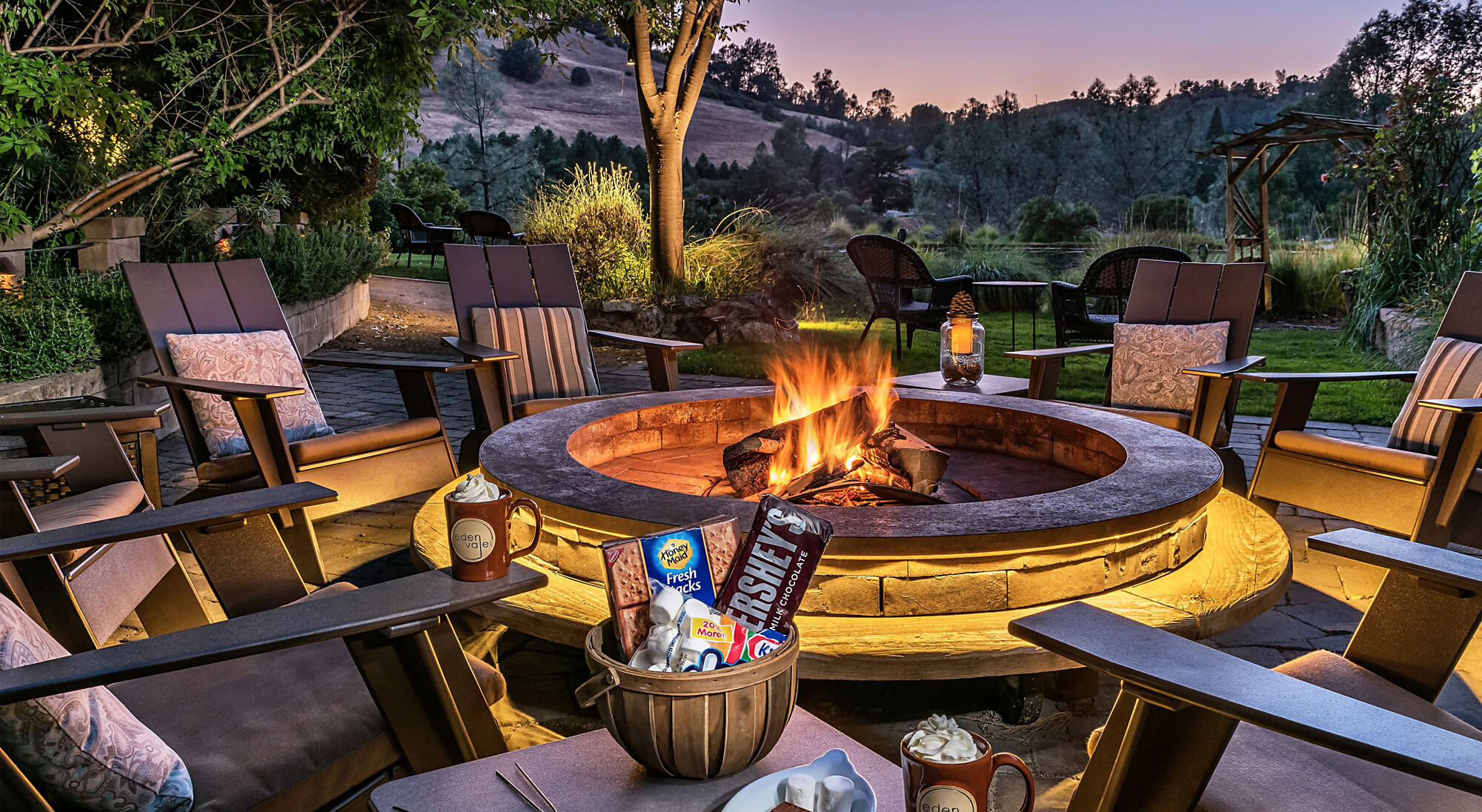 Cozy fire pit surrounded by chairs with ingredients to make s'mores