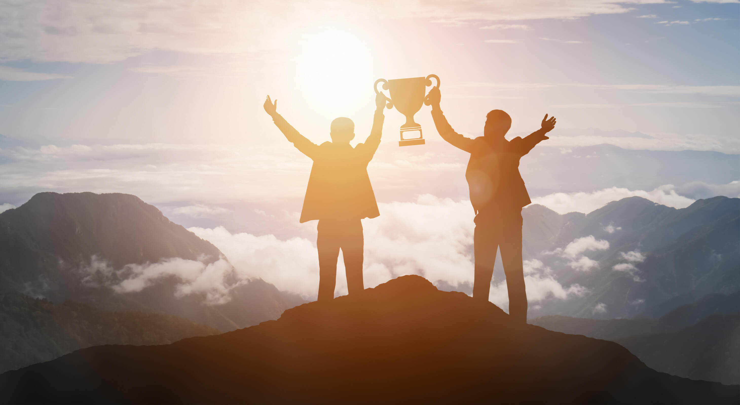 Two people winning on the top of a mountain
