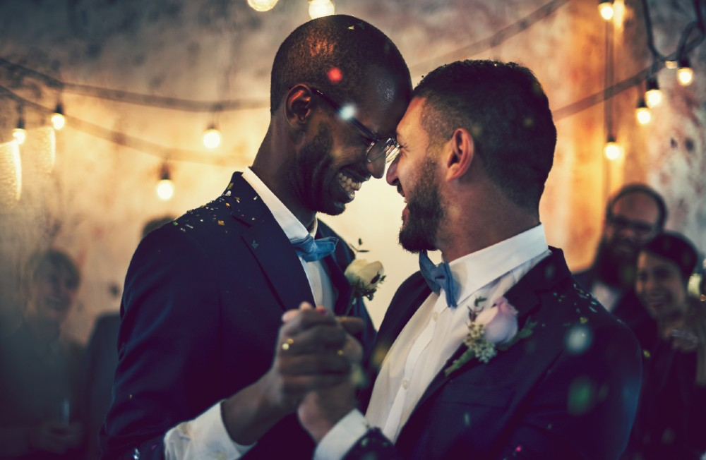 happy gay couple dancing at wedding