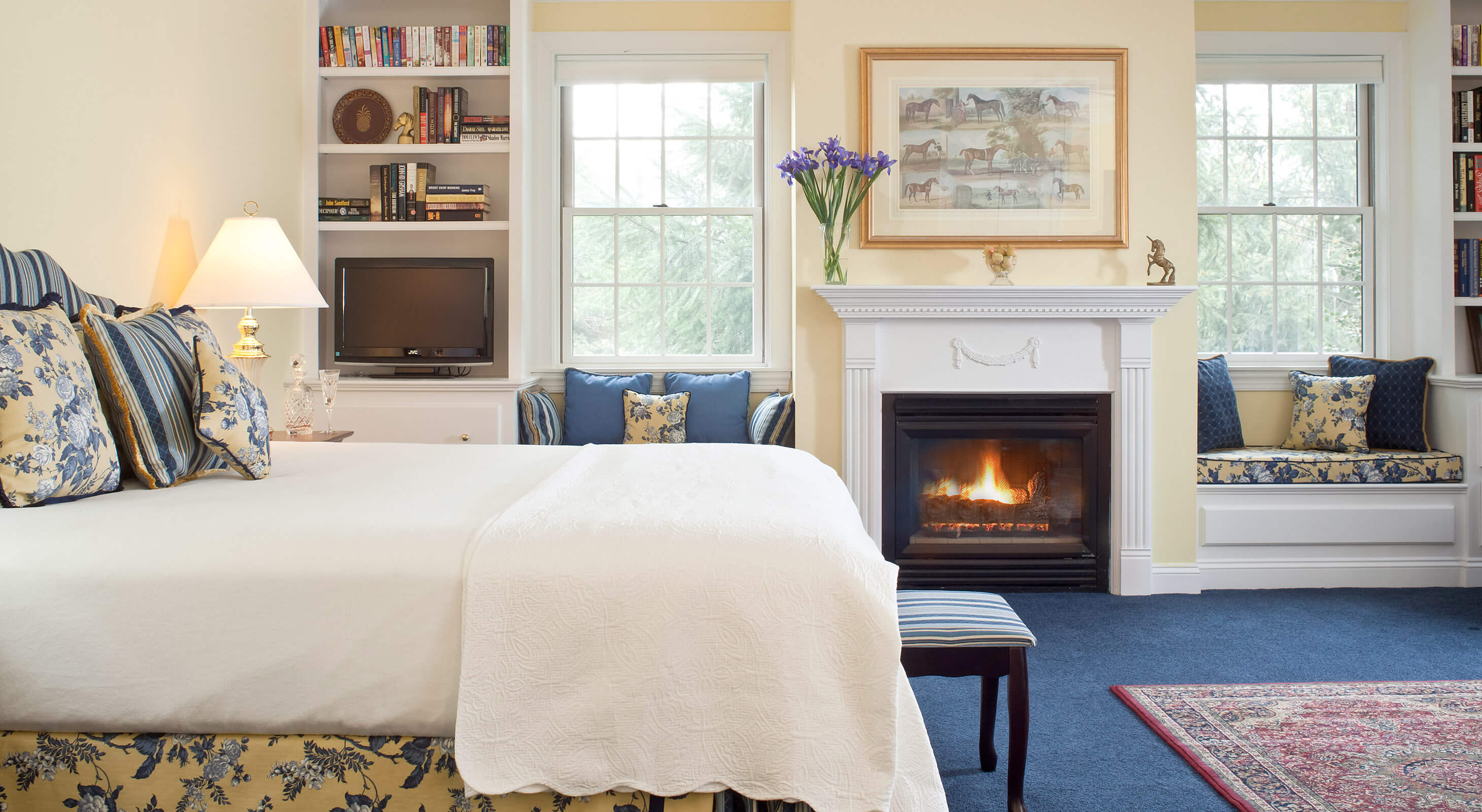 elegant guest room with blue carpet and fireplace