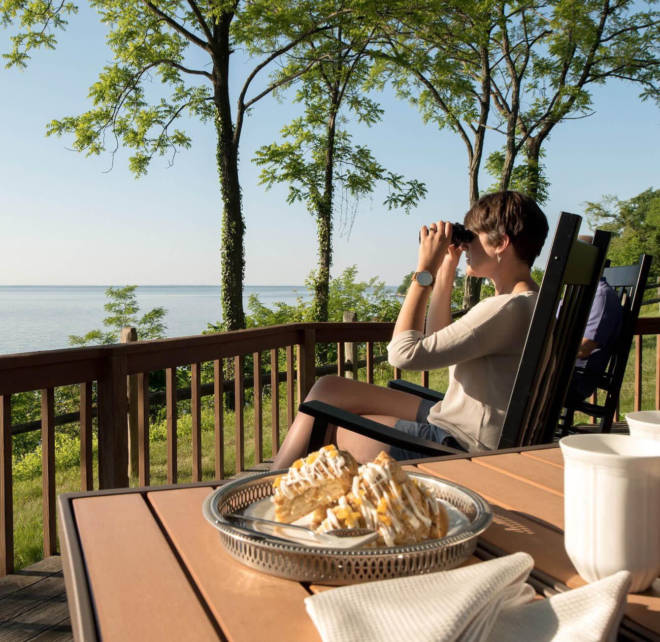 spacious waterfront inn with woman looking through binoculars