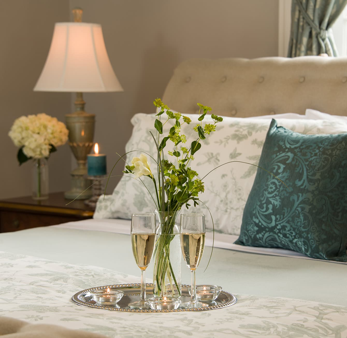champagne and flowers on a bed at Landmark Inn Cooperstown