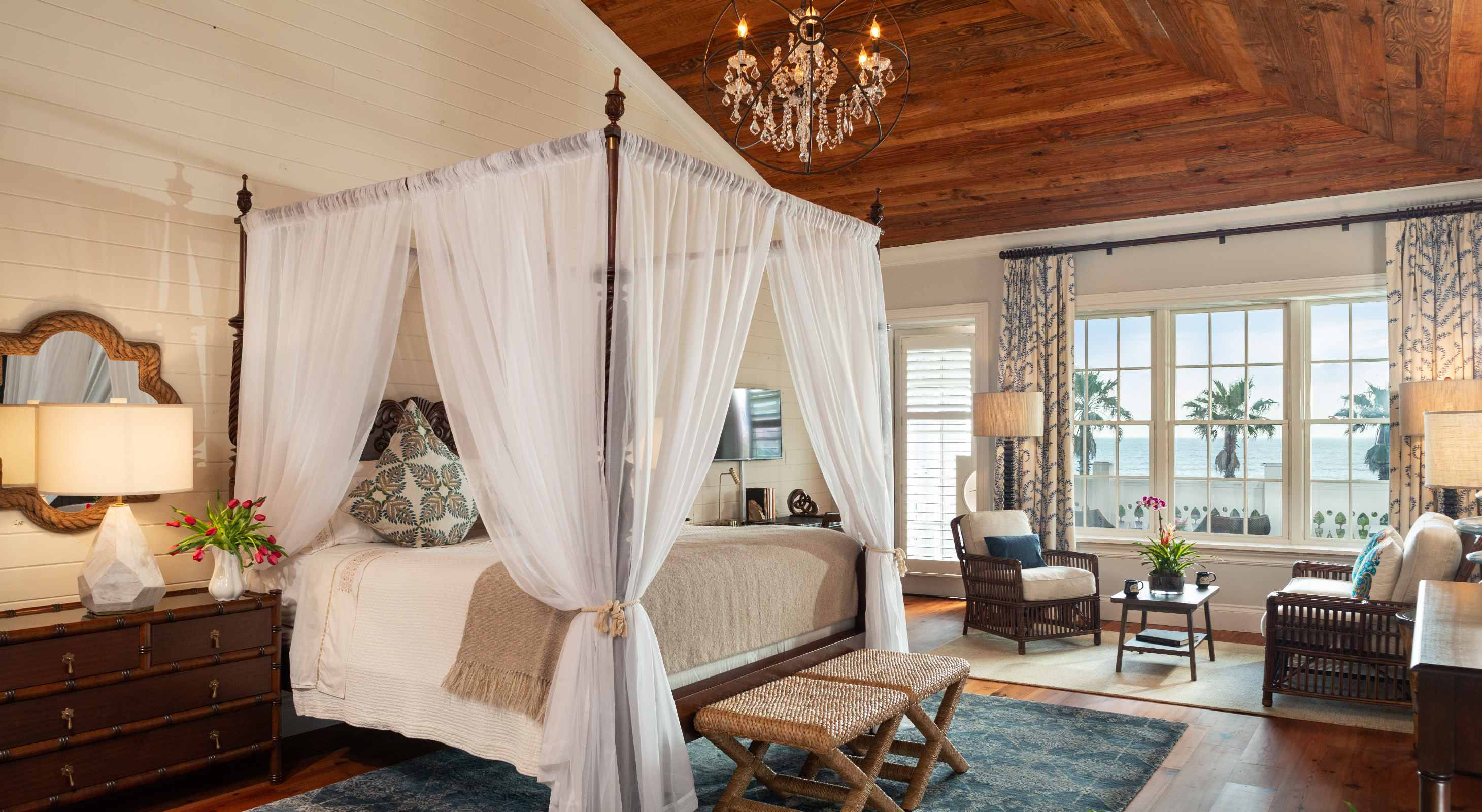 luxury guest room with four poster bed and windows with palm trees
