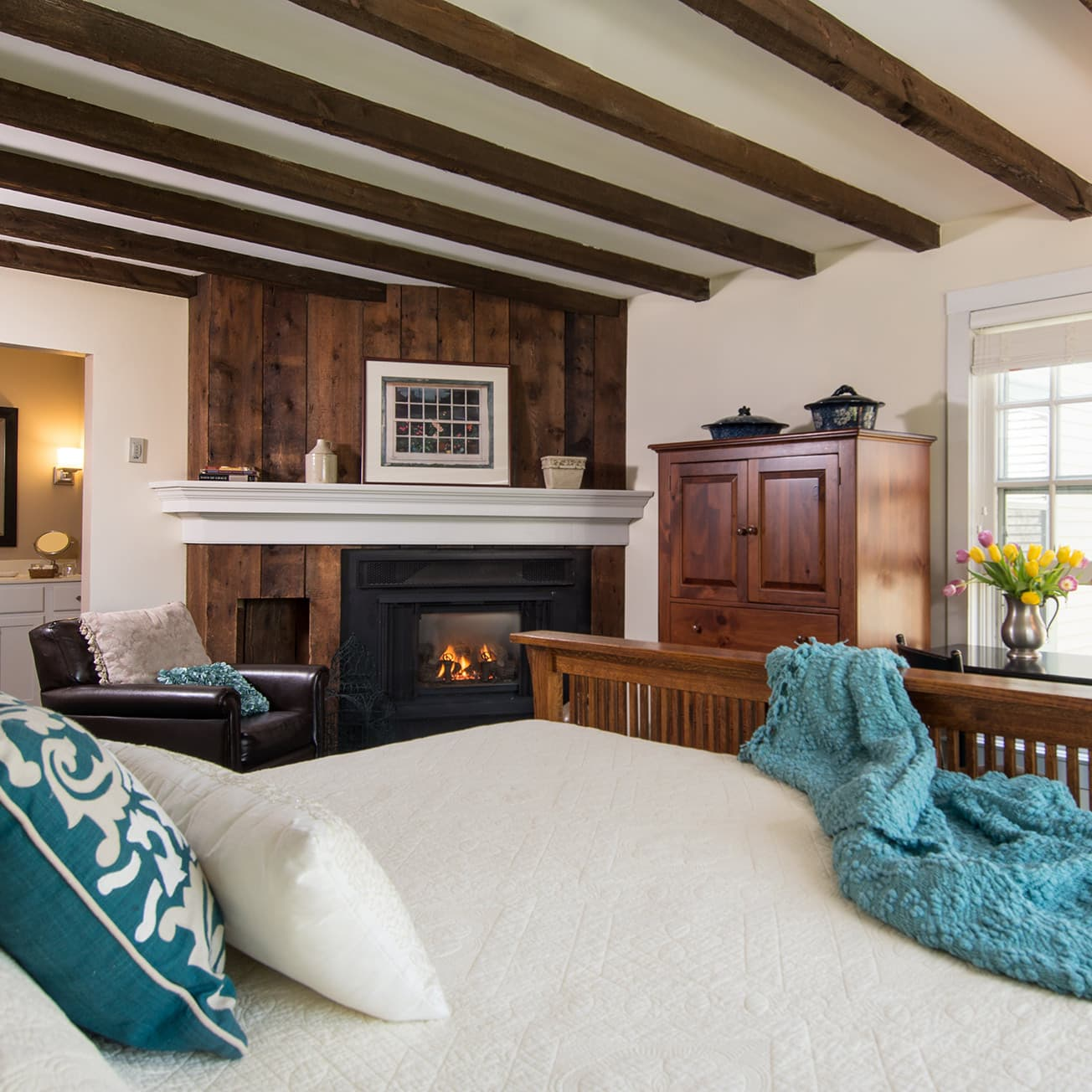 Room at the Chesterfield Inn with cozy bed and fireplace