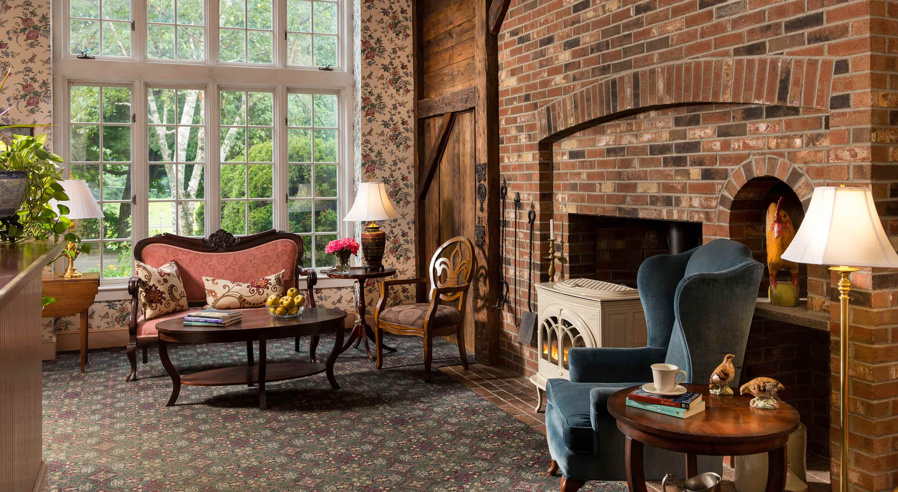 The Lobby of Chesterfield Inn with exposed brick and white stove, loveseat and chair